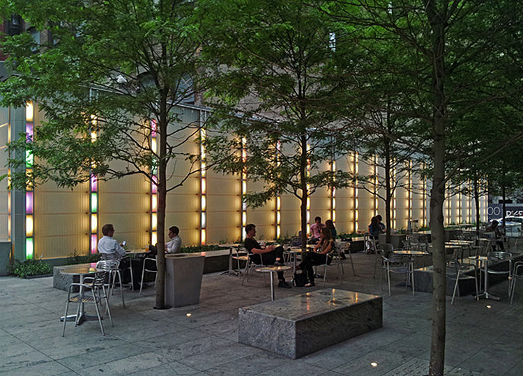 The 10,000 sq. ft. urban plaza features a reflecting pool, tree-lined promenade and an outdoor café.  An internally lit 220ft long and 20 ft. high glass screen provides consistent 3 fc light level throughout the plaza.