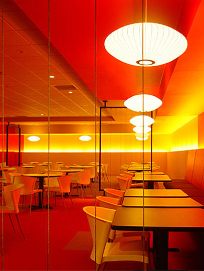 """Glowing, primary colors are the distinguishing feature of this low-budget, """"face-lift""""-type renovation project.  This effect is created by continuous fluorescent up-lighting concealed behind the banquettes, and further enhanced by the accents of singular, pendant lights."""