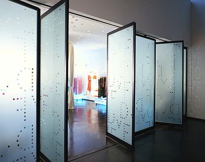 The motif of Diane von Furstenberg's dot logo begins on sandblasted glass doors of her retail showroom, and continues on the interior walls and ceiling. Diane von Furstenberg is inspired by the carved plaster and glass mosaics she saw while traveling in India and other exotic locations.