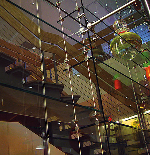 Two-story high structure of suspended glass shelves screens the view from the open space into the conference rooms of both levels.  The entire glass structure is subtly lit by an arrangement of deeply recessed fluorescent lights concealed along its vertical edge.