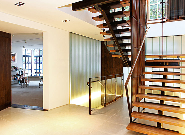 """A series of floor-concealed linear lights on the ground floor emphasize particular elements of the interior. When first seen through the etched-glass partitions of the vestibule, the lights appear at the """"wainscot"""" height, revealing the elevated level of the ground floor platform."""