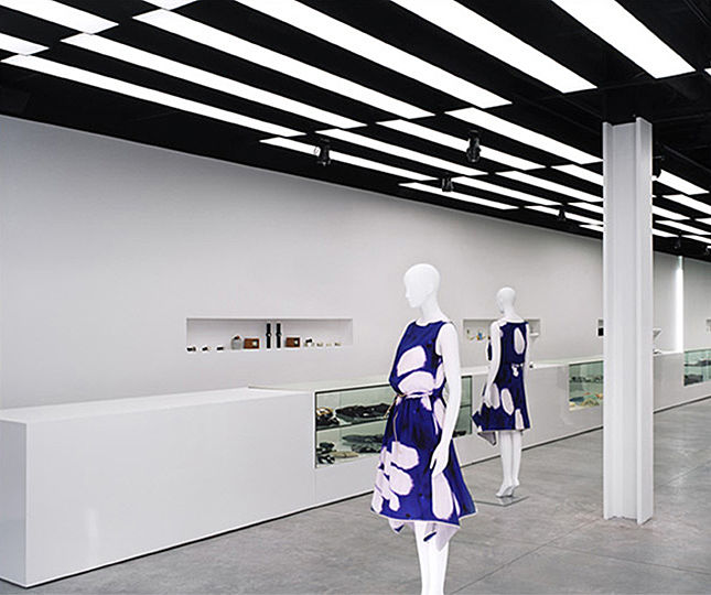 Each of the back-lit panels contains two 8-foot long fluorescent lights. The entire pattern of ceiling lights is divided into three interlocking parts which are controlled separately to provide additional flexibility when needed.  The cool ambience, created by the fluorescent lights, is complemented by warm metal halide track lights which are used for a variety of accessories and are selectively aimed at particular objects on display.