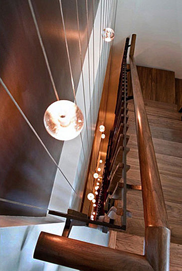 Thirty-three globe lights are suspended within the shallow space which separates the building's main stairway from the adjacent seven-story-high wall. The globes temporarily increase their light intensity in response to motion on the stairway.
