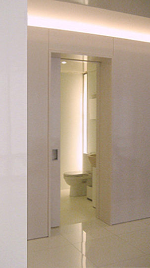 The bathrooms, with 8 ft. high ceilings, feel less confined thanks to their custom-made recessed vertical lights.