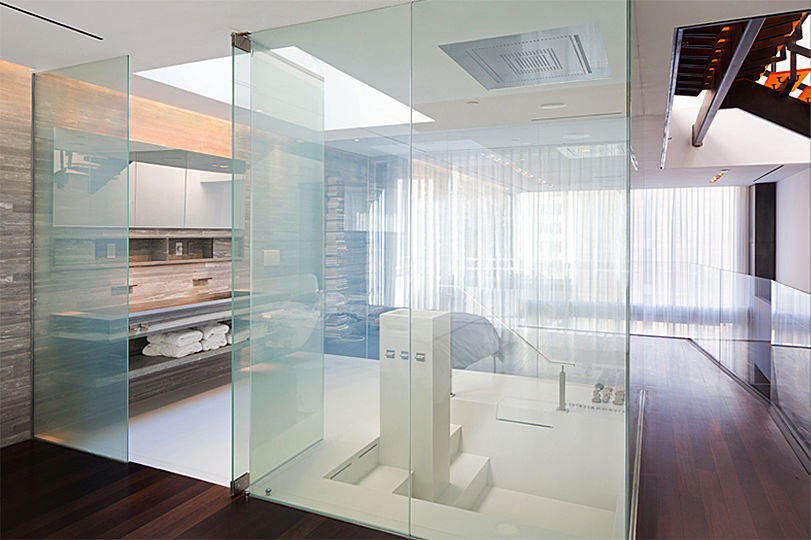 Smart glass panels enclose the master bathroom with its white Corian floor and sunken tub. Nothing interrupts the visual flow unless you touch the button that turns the clear panels opaque.