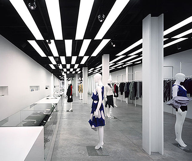 The implied lighting technique helps resolve the space's physical constraints. The building's ceiling, pipes, ducts, and power supply system are painted black. A black metal strut frame system hangs from the ceiling at a height of 10 feet above the floor. It supports the custom-made back-lit panels, as well as the lighting tracks.