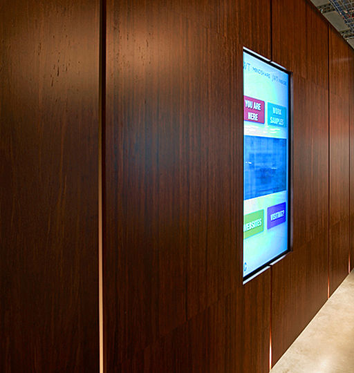 The building's service core is wrapped in floating panels of bamboo plywood, which accommodates all sorts of narrative mediums: video monitors, projection screens, LED displays and whiteboards. The circulation area around the service core is lit with a row of seamless fluorescent lights concealed at the bottom edges of the floating panels.