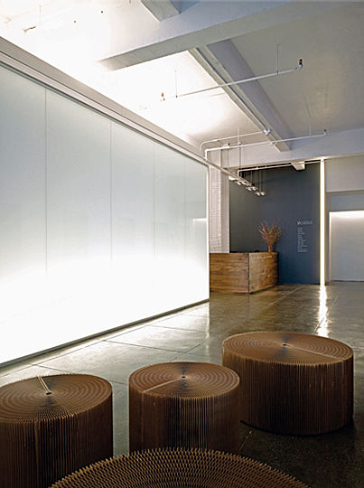 """Following the architect's approach, the lighting scheme consists of a number of lighting applications, each used in response to a particular architectural form: The free-standing accent wall of the entry with its vertical lights is facing the glowing """"glass house"""" of the library, which is adjacent to the smaller """"houses"""" of supporting facilities with their up-lit ceiling planes. The building's shell structure, being left exposed, spans over the """"interior architecture""""."""