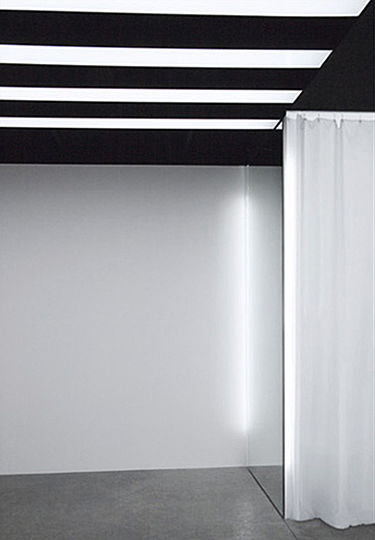 Deeper into the store, the horizontal and highly graphic lighting pattern is replaced with the glow of vertically-mounted fluorescent lights.  The draped, white gauze curtain of the fitting area is softly back-lit by the bare fluorescent tubes mounted at the front edges of the free-standing mirrored partitions.  Similar fluorescent tubes are placed on the opposite edge of each partition, along the perimeter wall.  The placement of the fixtures accentuates the freestanding character of the partitions, while their dimensions and finish match that of the partitions, contributing to the minimalist character of the design scheme.